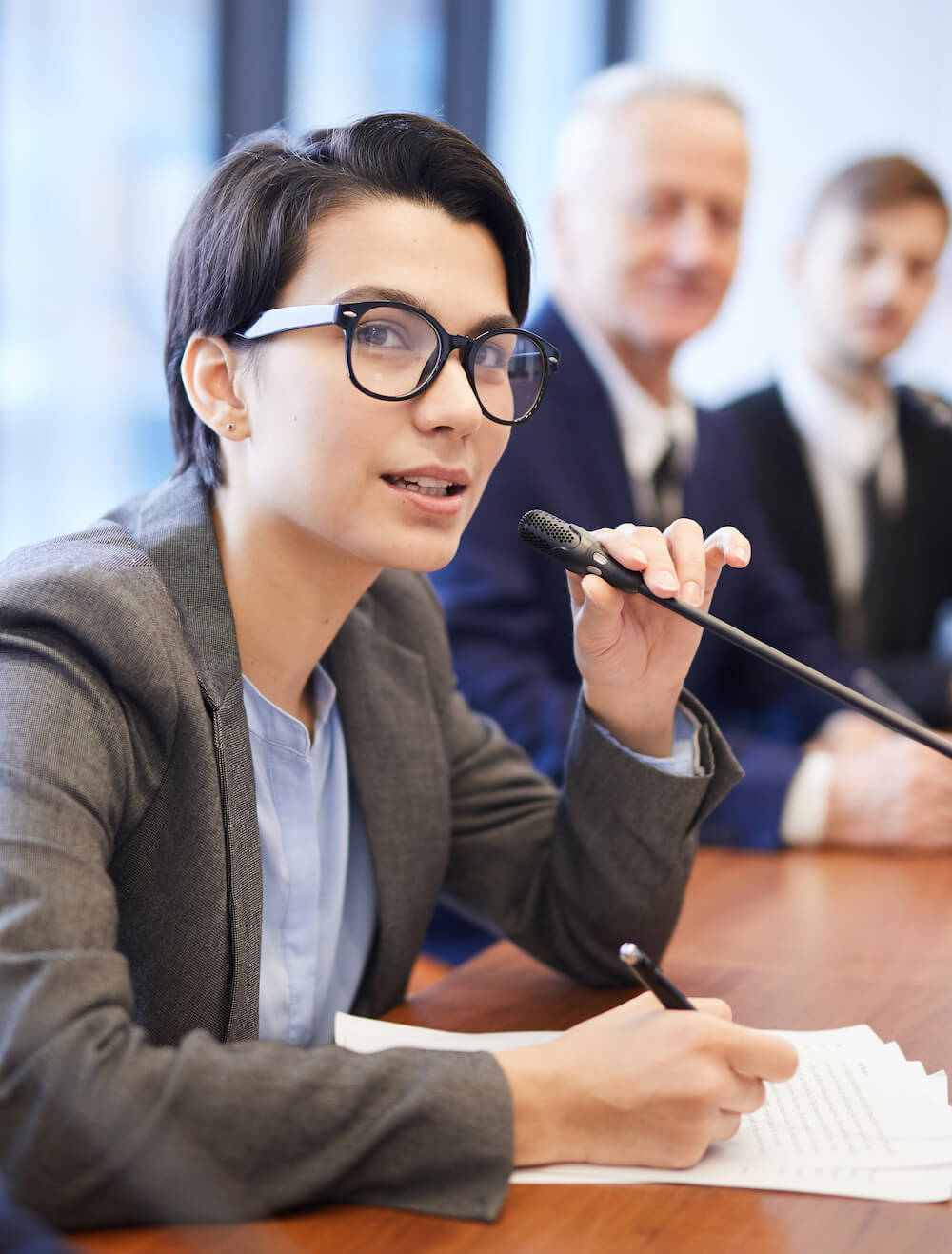 Portrait of young businesswoman speaking to microphone during conference and taking notes while sitting in row with colleagues , copy space